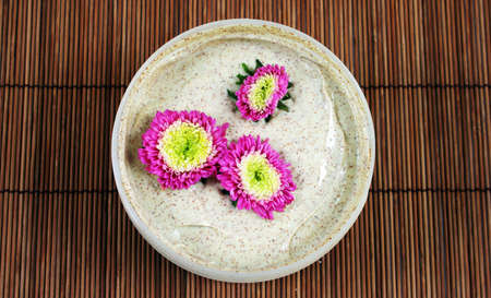 body scrub: Spa and beauty products - body scrub with pink flowers.
