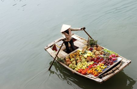 tourism industry: Woman selling fruit from a boat on Halong Bay, Vietnam - travel and tourism. Stock Photo