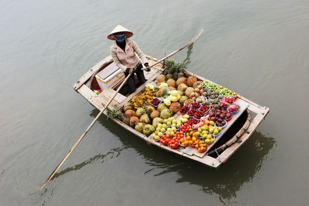 adult vietnam: Woman selling fruit from a boat on Halong Bay, Vietnam - travel and tourism. Stock Photo