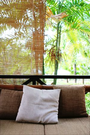 Sofa and pillows with a tropical garden in the background. photo