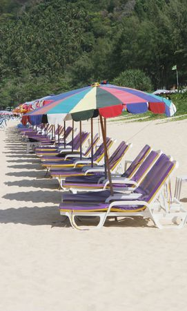 Rows of colorful beach chairs and umbrellas at the beach. Stock Photo - 2735457