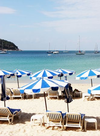 Blue and white beach umbrellas overlooking the sea. photo