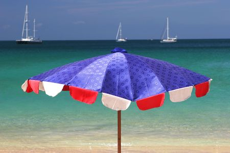 Bright blue and red beach umbrella overlooking the ocean on a summer day. Stock Photo - 2735449