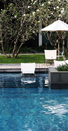 Deck chairs next to a swimming pool. photo