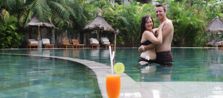 Happy couple in the swimming pool with a cocktail in the foreground. photo
