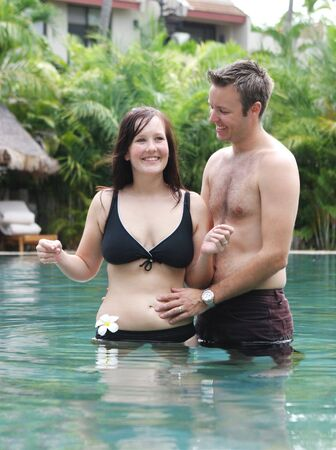 Happy young couple relaxing in a swimming pool. photo