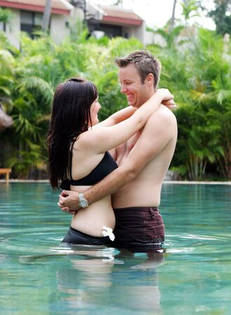 Happy young couple relaxing in a swimming pool.