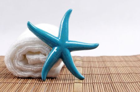 Blue starfish and white fluffy towel - spa and beauty. photo
