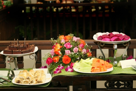cuisine entertainment: Tropical fruit and desserts on a table with a rose floral arrangement. Stock Photo