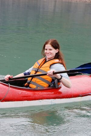 lifejacket: Happy woman kayaking in a lake - health and fitness.