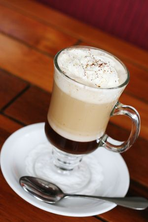 caffiene: Glass of hot coffee with cream on top. Stock Photo