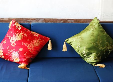 Red and green oriental cushions on a sofa. photo