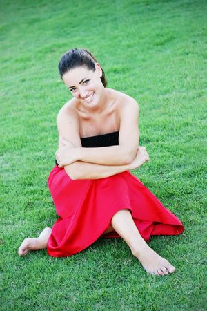 strapless: Beautiful young woman sitting outside on the grass. Stock Photo