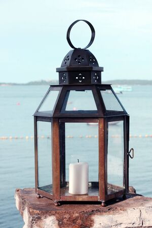 Candle in a holder overlooking the ocean.