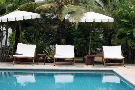 Deck chairs and umbrellas next to a swimming pool. photo