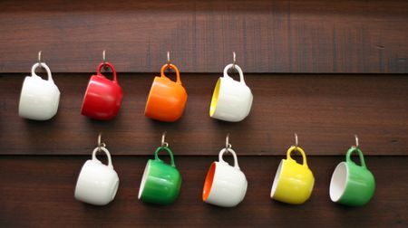 homeware: Colorful coffee cups hanging on a wall.