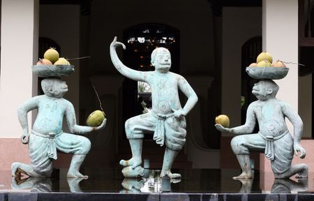 fine cane: Monkey statues holding fruit in a water garden.