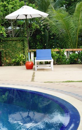 decor residential: Deck chairs and umbrellas next to a swimming pool. Stock Photo