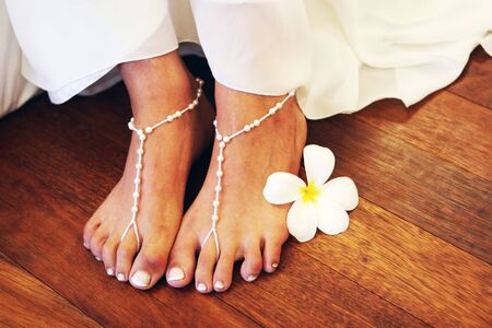 Close-up of a bride wearing bead sandals on her feet.