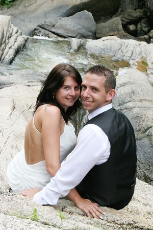 Beautiful bride and groom sitting on a rock by a waterfall. Stock Photo - 3497971