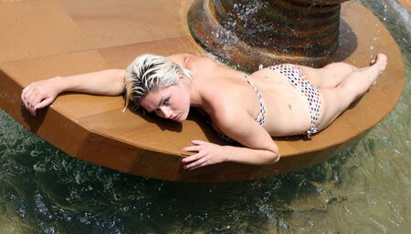 Beautiful young woman wearing a bikini by the swimming pool. Stock Photo - 3525660