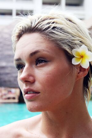 Close-up portrait of a beautiful blond woman with a flower in her hair. photo