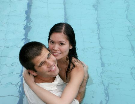 Bride and groom in the swimming pool - trash the dress trend. photo