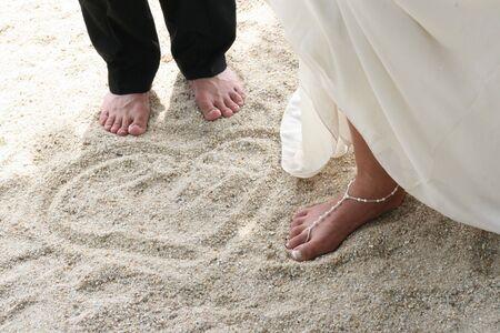 sexy f�sse: Braut und Br�utigam neben einer Liebe Herzen Muster in den Sand stecken.