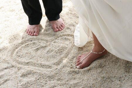 adult's feet: Bride and groom next to a love heart pattern in the sand.