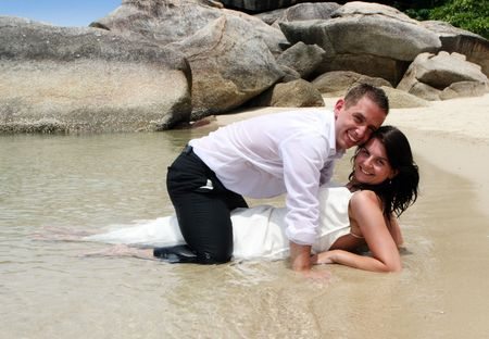 Bride and groom in the ocean during trash the dress session. photo