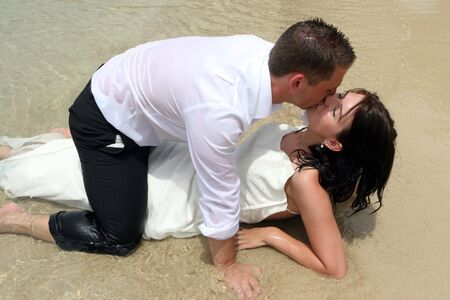 trash the dress: Sexy bride and groom kissing at the beach. Stock Photo