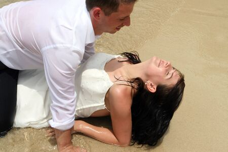 trash the dress: Bride and groom in the ocean during a trash the dress session. Stock Photo