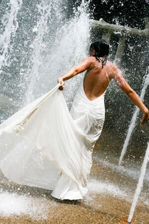 Beautiful young bride playing in a waterfall on her wedding day. photo