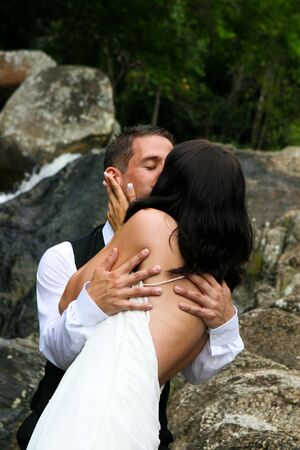 trash the dress: Happy bride and groom kissing on top of a mountain. Stock Photo