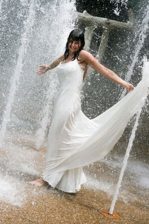 trash the dress: Beautiful young bride playing in a waterfall on her wedding day.