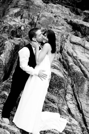 Happy bride and groom kissing on top of a mountain. photo