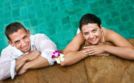 Happy bride and groom in the swimming pool during a trash the dress photo shoot. photo