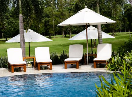 pool deck: Deck chairs by a beautiful swimming pool.