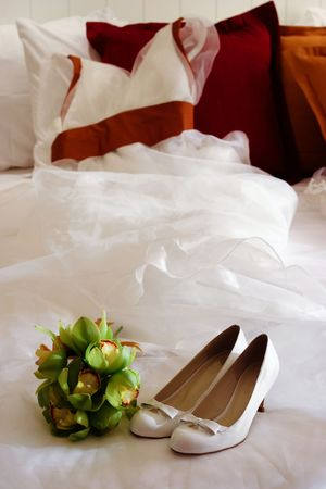 Wedding dress with bouquet and shoes in the foreground. photo