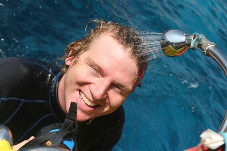 skindiver: Happy scuba diver having a shower on a boat after a dive.