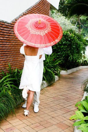Bride and groom with a bright red parasol. photo