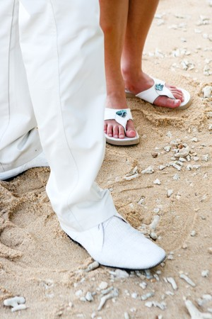 sandels: Bride and grooms feet during a wedding ceremony on the beach. Stock Photo