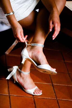 Close-up of a bride doing up her shoes. photo