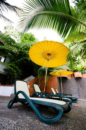 Deck chairs and a bright yellow umbrella on a summer day.