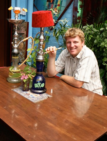 Young caucasian man smoking a traditional Middle Eastern hookah. photo