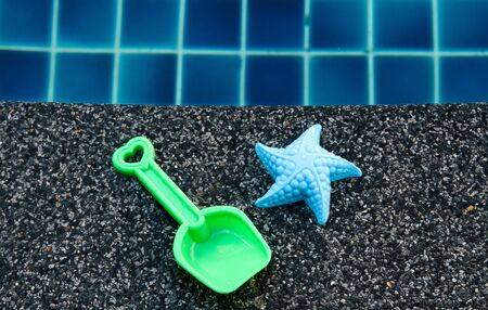 Childs toy starfish and spade by the swimming pool edge. photo