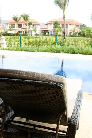Swimming pool with deck chairs overlooking a lush garden. 스톡 콘텐츠