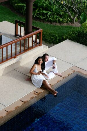 Attractive multicultural couple by the swimming pool. photo