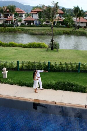 Attractive multi-cultural couple by the swimming pool. photo