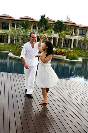 Attractive multi-cultural couple dancing by the swimming pool. photo